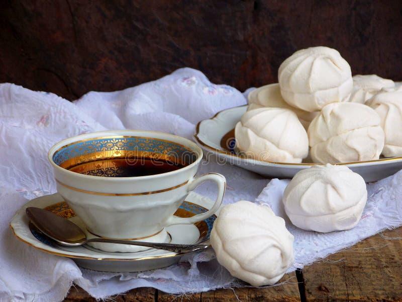 Marshmallow do russo, zéfiro do chocolate, merengue e xícara de café brancos doces no fundo de madeira fotos de stock royalty free