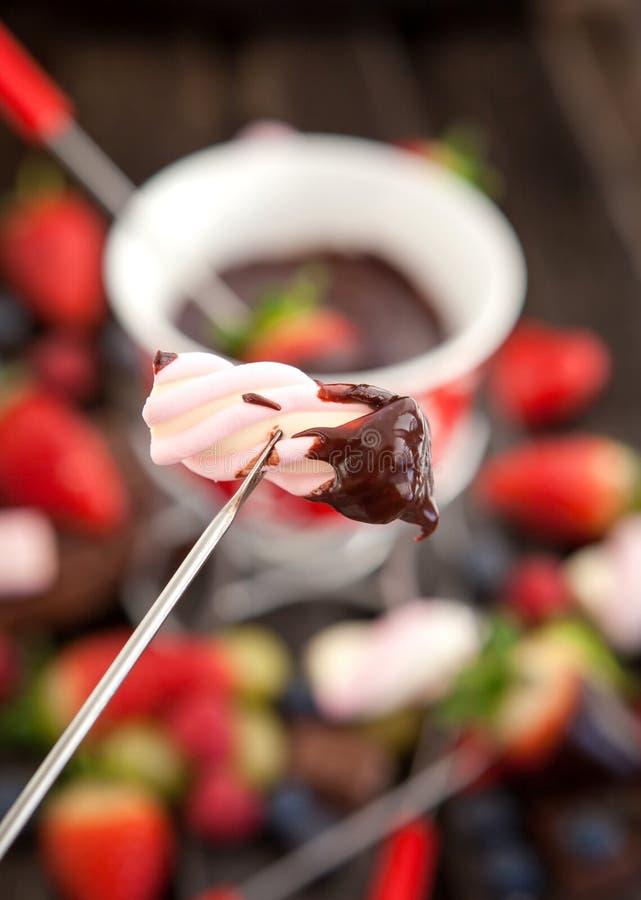 Marshmallow mergulhado no fondue de chocolate imagem de stock