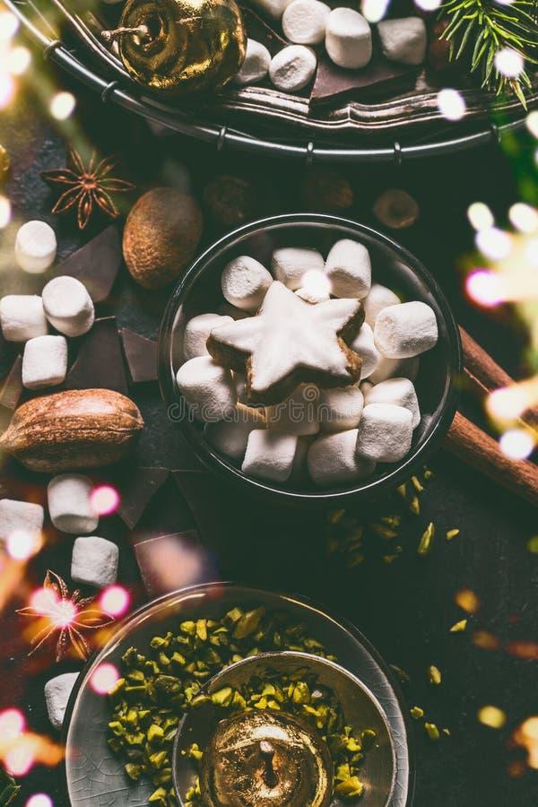Marshmallow- och julstjärnakakor med choklad och kryddor: kanel, anis och cardamon med muttrar på mörk bakgrund royaltyfria foton