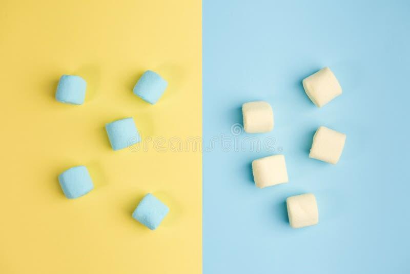 Marshmallow på blåa och gula bakgrunder Tv? f?rgar arkivbilder
