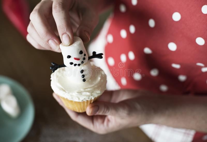 Marshmallow snowman Christmas cupcake decorating royalty free stock image