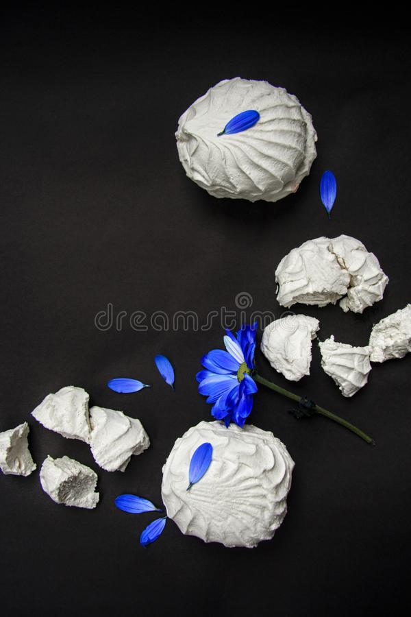 Marshmallow whole and broken and flower with blue petals. Flat lay royalty free stock photos