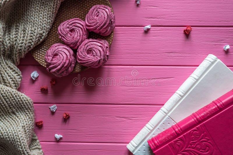 Marshmallower och böcker på en rosa trätabell arkivbild