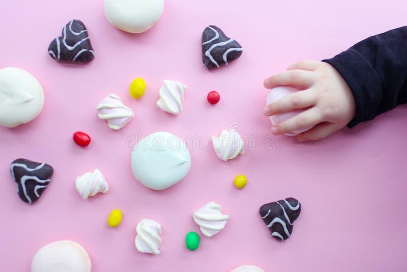 Marshmallower, pepparkakan och godisen ordnas i en cirkel på en rosa bakgrund, bästa sikt sötsaker i en cirkel royaltyfria foton