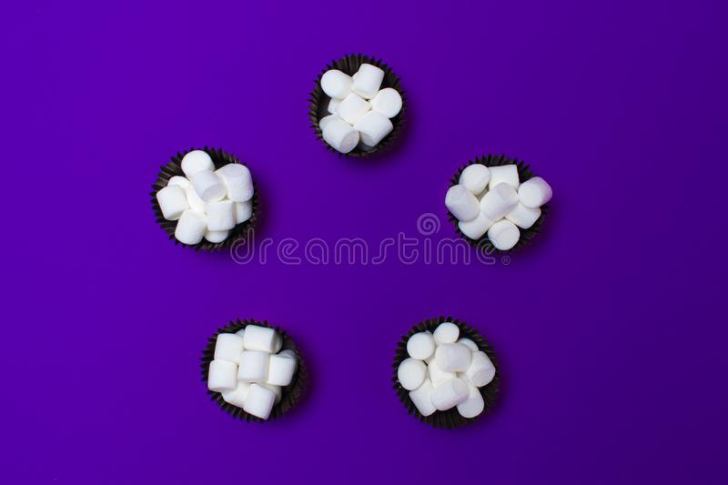Marshmallows στις μορφές για τα κέικ σε ένα πορφυρό υπόβαθρο, πέντε κομμάτια Τακτοποιημένος σε έναν κύκλο επάνω από την όψη στοκ φωτογραφία με δικαίωμα ελεύθερης χρήσης
