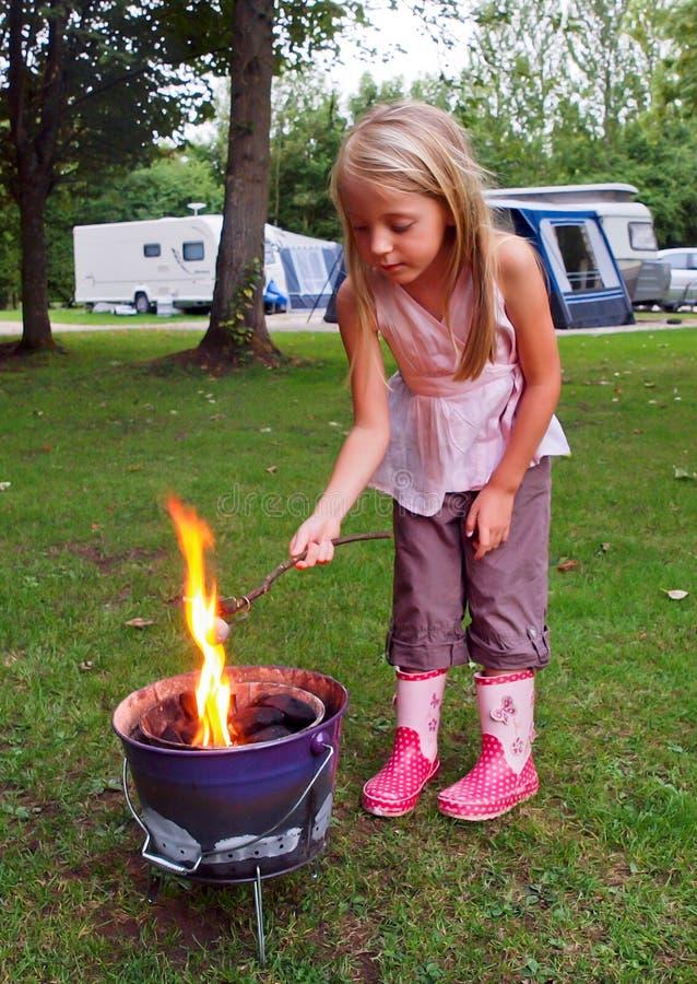 marshmallows κοριτσιών πυρκαγιάς στρατόπεδων ψήσιμο στοκ εικόνες