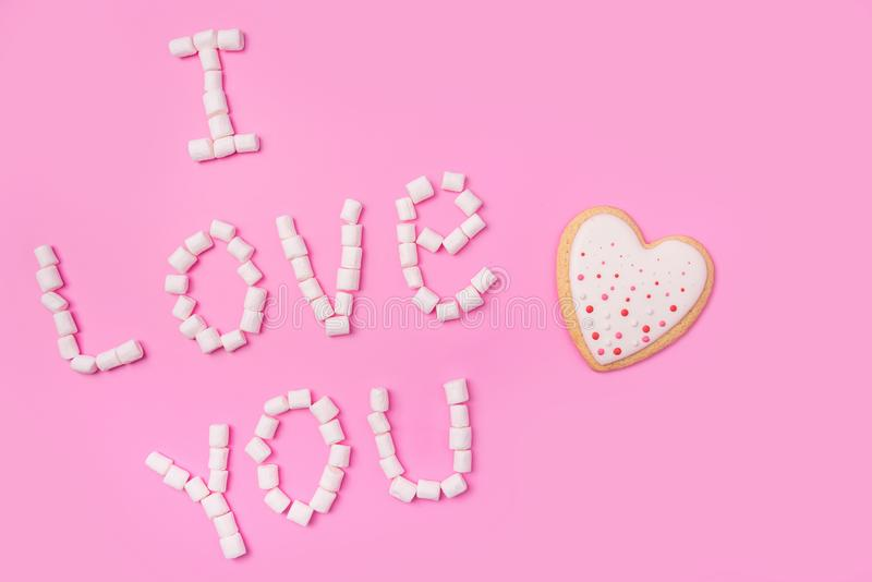 Marshmallows στο ρόδινο υπόβαθρο με το σημάδι στα αγγλικά σ' αγαπώ Επίπεδος βάλτε ή τοπ άποψη Το υπόβαθρο ή η σύσταση ζωηρόχρωμου στοκ εικόνες
