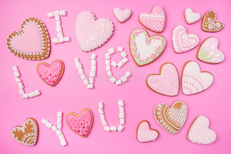 Marshmallows στο ρόδινο υπόβαθρο με το σημάδι στα αγγλικά σ' αγαπώ Επίπεδος βάλτε ή τοπ άποψη Το υπόβαθρο ή η σύσταση ζωηρόχρωμου στοκ εικόνα