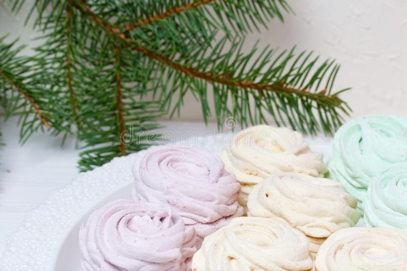 Desserts for winter parties. Sweets and spruce branch. Marshmallows on a background of fir branches. Desserts for winter parties stock photo