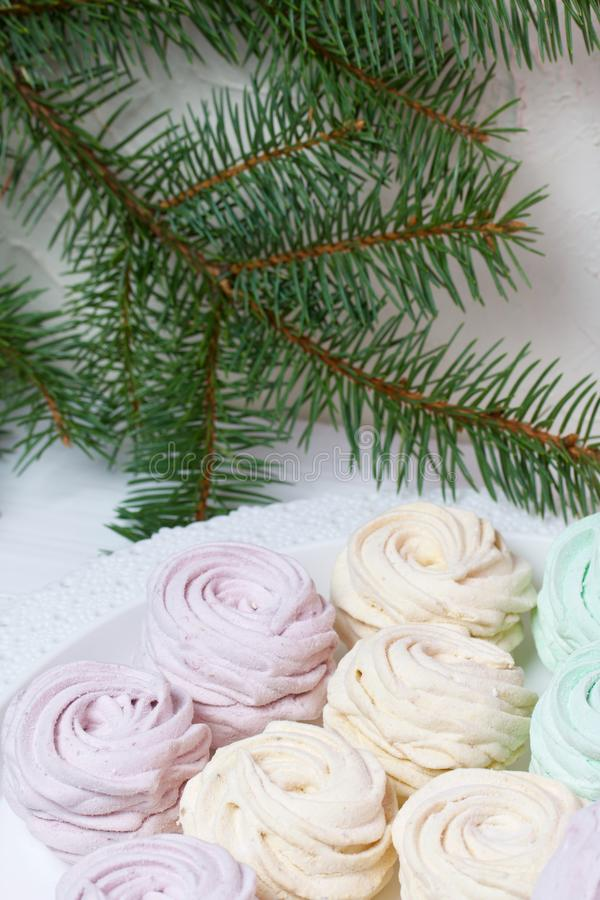 Desserts for winter parties. Sweets and spruce branch. Marshmallows on a background of fir branches. Desserts for winter parties stock photography