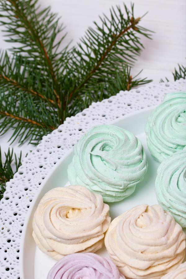 Desserts for winter parties. Sweets and spruce branch. Marshmallows on a background of fir branches. Desserts for winter parties royalty free stock image