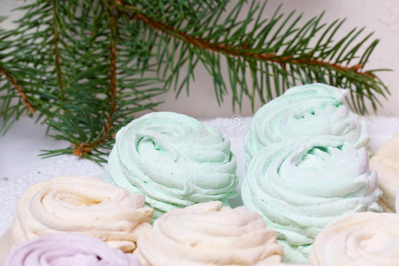 Desserts for winter parties. Sweets and spruce branch. Marshmallows on a background of fir branches. Desserts for winter parties royalty free stock photos