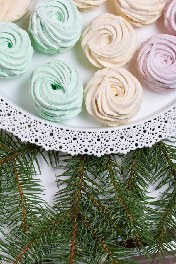 Desserts for winter parties. Sweets and spruce branch. Marshmallows on a background of fir branches. Desserts for winter parties stock image