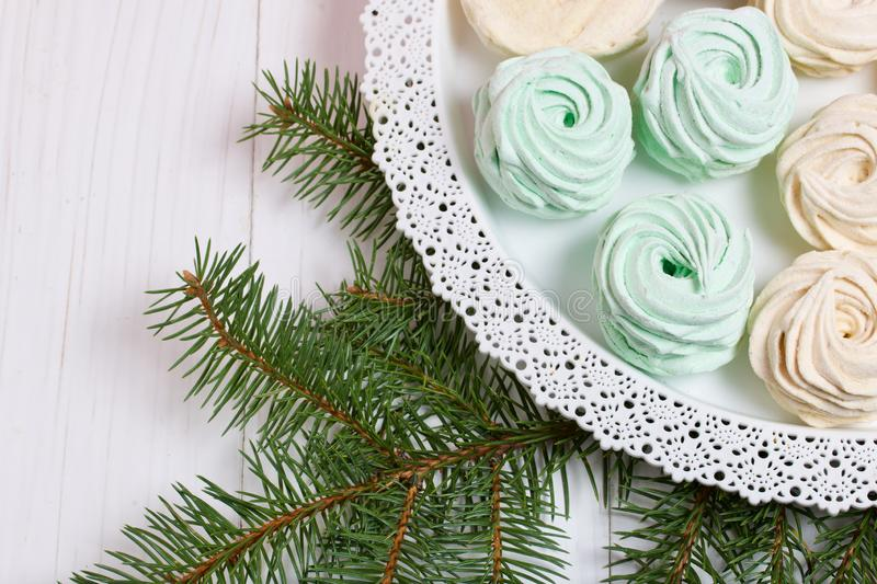 Desserts for winter parties. Sweets and spruce branch. Marshmallows on a background of fir branches. Desserts for winter parties royalty free stock images