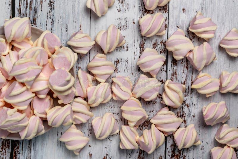 Marshmallows cor-de-rosa com ondas amarelas, no fundo de madeira claro Derramado da placa fotografia de stock