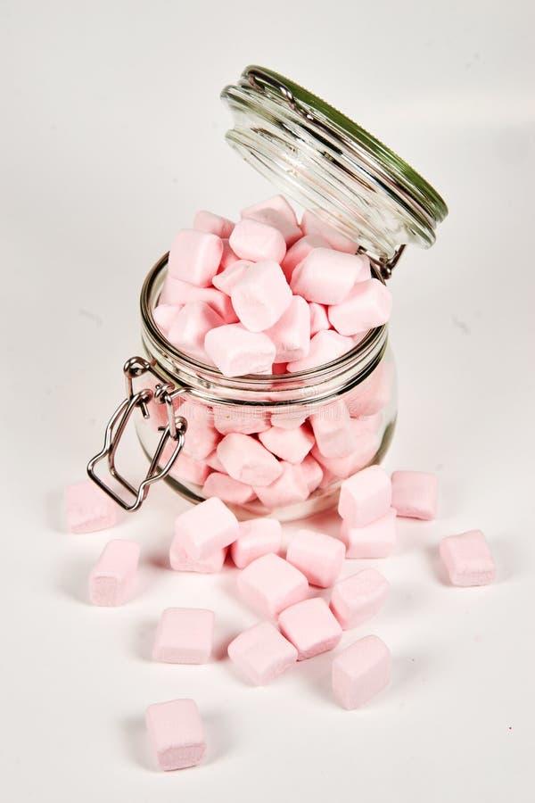 Marshmallows cor-de-rosa no frasco de vidro, no fundo branco fotografia de stock
