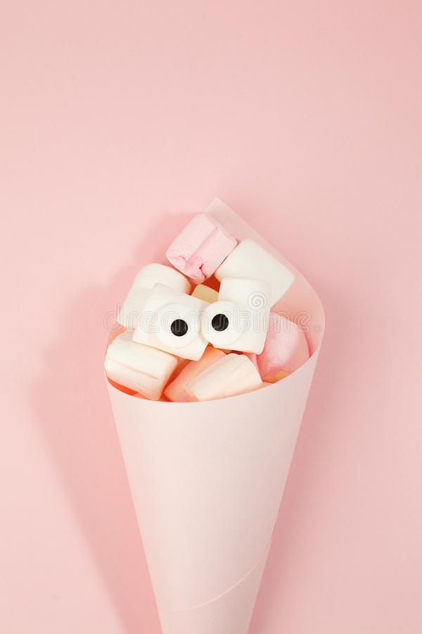 Marshmallows with eyes in paper cone. Funny kawaii emoji face. Cute cartoon character. Minimal summer flat lay design. Sweet food. Pink background, monochrome royalty free stock photo