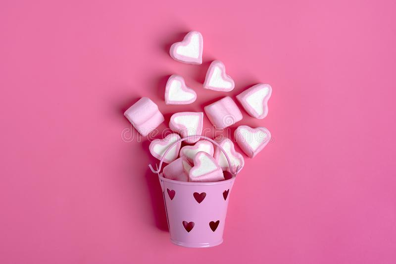 Marshmallows and heart shaped candies spilled from a pink iron bucketon a pink background Happy Valentine`s Day royalty free stock photography