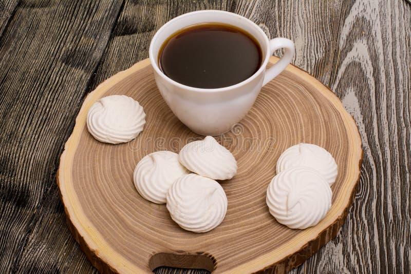 Marshmallows i kubek kawa na saw cięciu drzewo na drewnianym obrazy royalty free