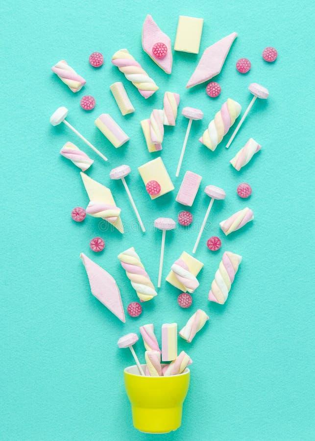 Marshmallows i lolly wystrzały wybucha od żółtej filiżanki, jaskrawy pastelu temat zdjęcia stock