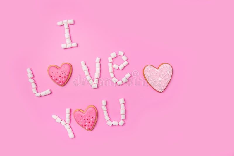 Marshmallows na różowym tle z podpisują Angielskiego wewnątrz Kochają Was Ja Mieszkanie nieatutowy lub odgórny widok Tło lub teks zdjęcie stock