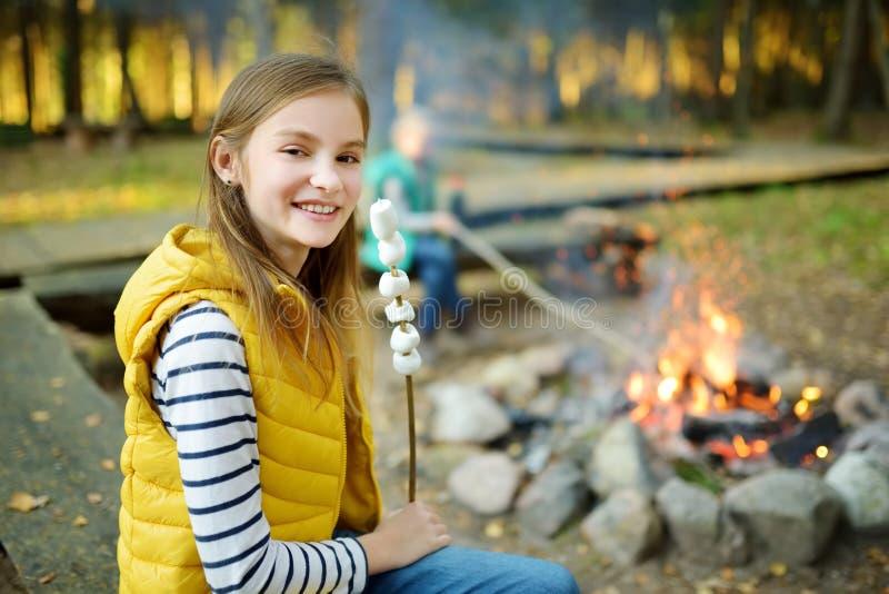 Marshmallows preteen bonitos da repreensão da menina na vara na fogueira Criança que tem o divertimento no fogo do acampamento Ac foto de stock