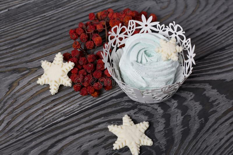 Marshmallows and snowflakes from marshmallows. Nearby dry rowan berries. On old pine boards painted black.  stock photography