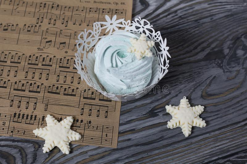 Marshmallows and snowflakes from marshmallows. On old pine boards painted black.  stock images