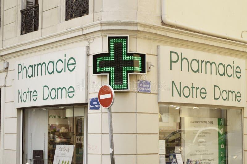 Marsiglia, Francia - 12 ottobre 2018: primo piano dell'incrocio verde principale, simbolo della farmacia, all'angolo di architett immagini stock libere da diritti