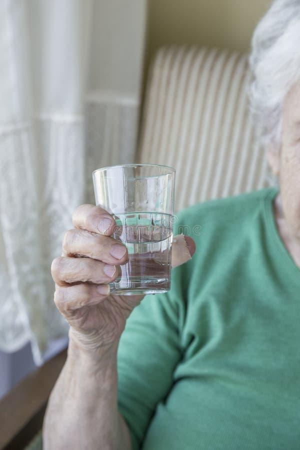Marszcząca ręka starsza osoba trzyma szkło woda fotografia stock