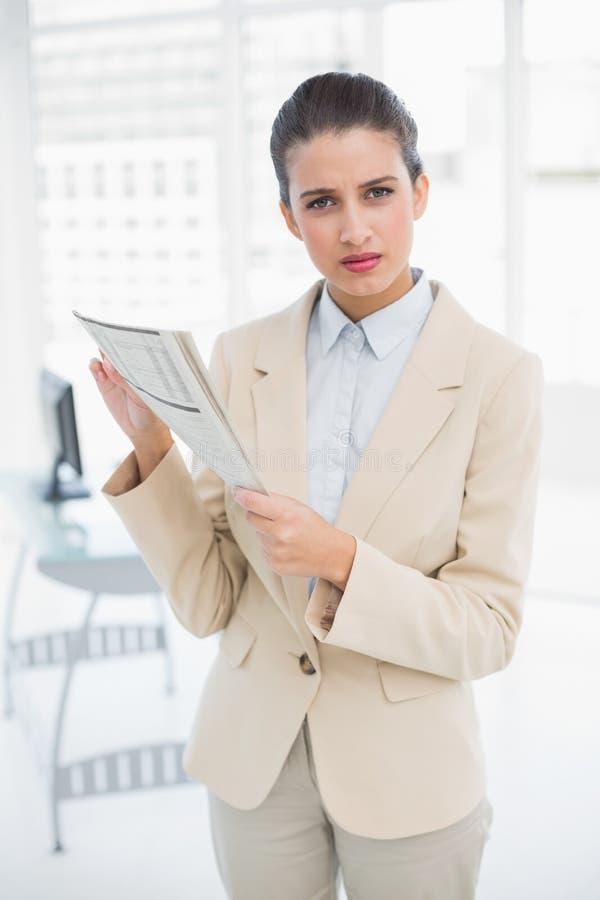 Marszczyć brwi mądrze brown z włosami bizneswomanu trzyma gazetę fotografia royalty free