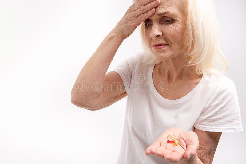Marszczyć brwi starej kobiety utrzymuje lekarstwa zdjęcie stock