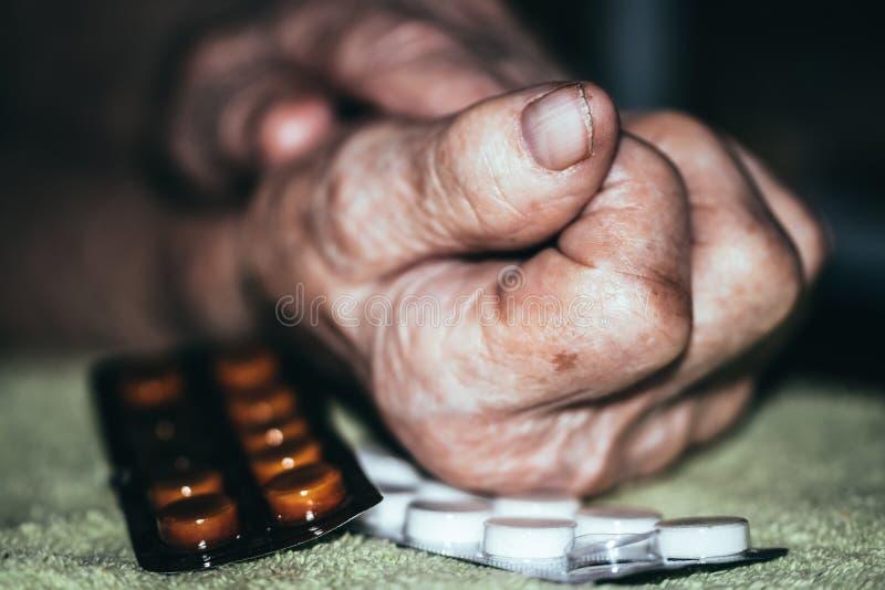 Marszczyć ręki stara chora kobieta i pigułki zdjęcie royalty free
