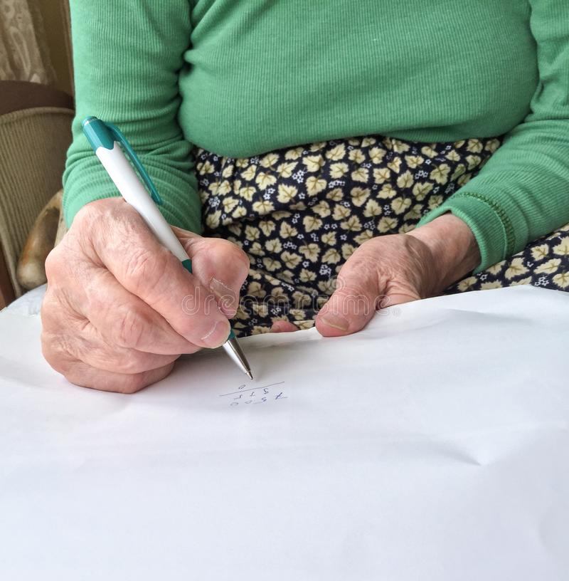 Marszczyć ręki starsza kobieta pisze na białej księdze zdjęcia stock