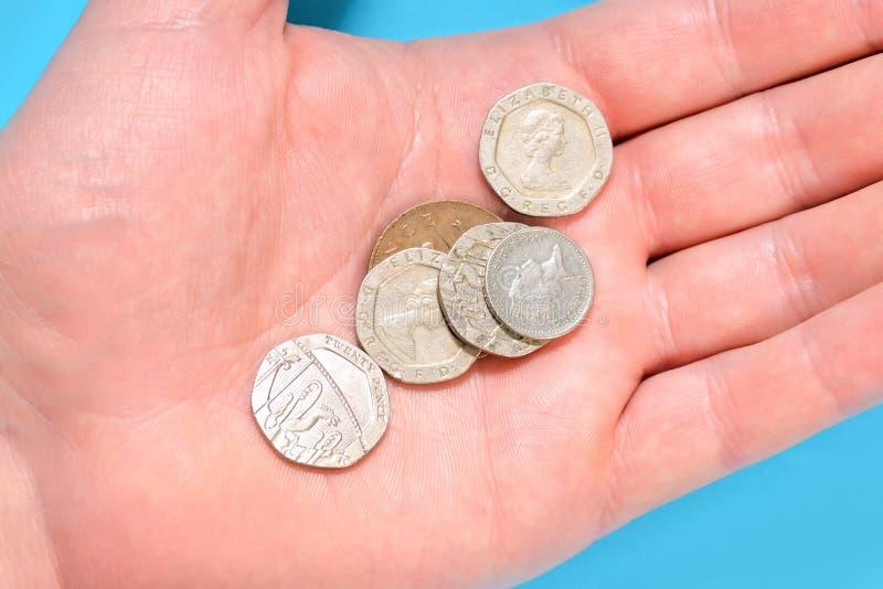 Martèle des pièces de monnaie de penny sur une paume d'une main d'homme photographie stock