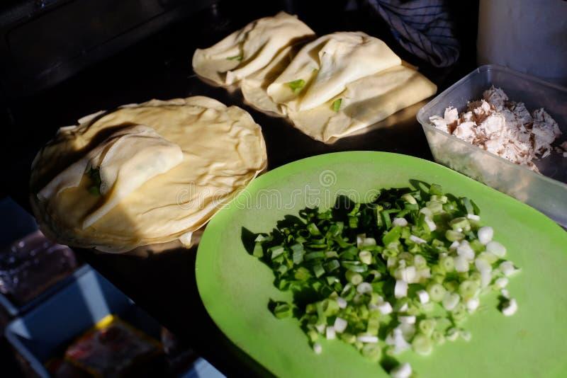 Martabak ingredienser, berömd vikt repedisk som fylls med kryddor, ägg, salladslökar och snitt av kött arkivfoto