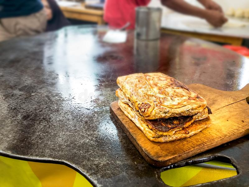 Martabak Telor oder gestopftes Omelet Pancake Fried Brot. Eine traditionelle Minang- oder Padang-Küche auf dem flachen Bratpfan stockbild