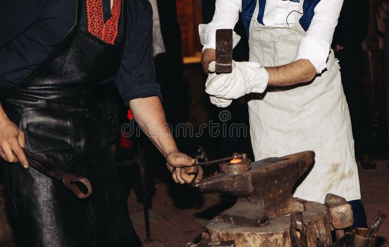 Marteau d'un rouge ardent en fer à cheval d'enclume de fer de forgeron photographie stock