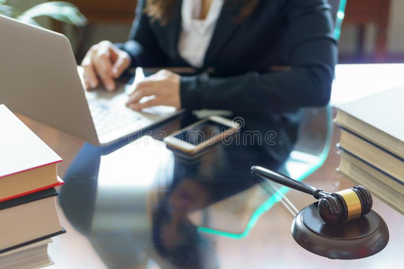 Marteau et avocat de juge travaillant sur un ordinateur portable dans le bureau images stock