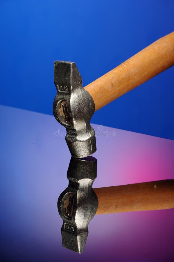 Marteau lourd sur la surface du verre, réflexion en verre, fond de couleur verre résistant aux chocs Poignée en bois images stock