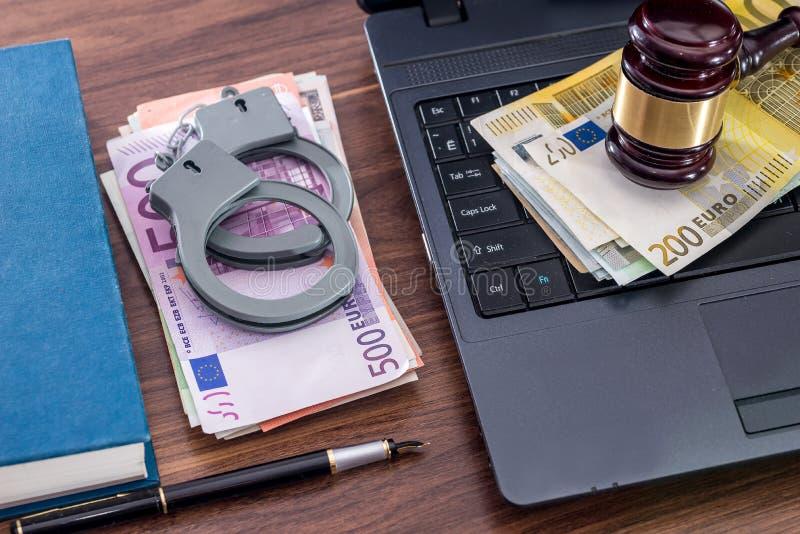 Marteau, menottes et factures en bois d'euro, ordinateur portable image stock