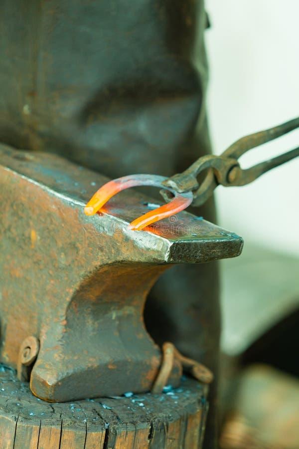 Martelant rougeoyer en acier - à il faut battre le fer quand il est chaud image stock