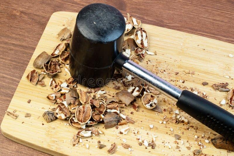 Martelez et avez écrasé les écrous sur une planche à découper sur un fond en bois image stock
