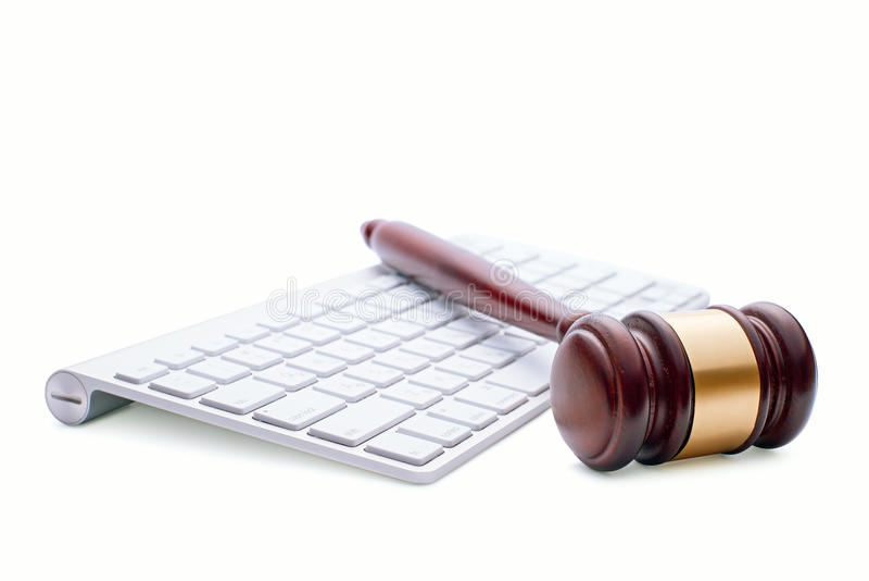 Martelletto di legno su una tastiera di computer bianca immagini stock