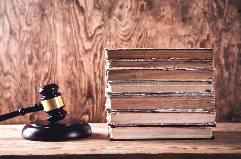 Martelletto e libri di legno del giudice sullo scrittorio di legno Legge e giustizia fotografia stock