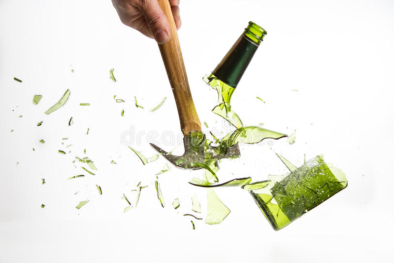 Martelli la rottura che una bottiglia di vetro verde ha isolato su fondo bianco fotografia stock libera da diritti
