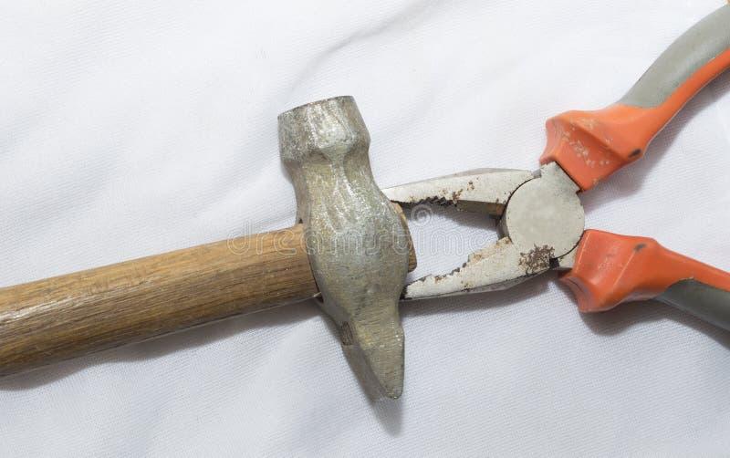 Martello e pinze su una superficie bianca Il concetto di litigio familiare, le pinze afferrano un martello alla testa immagine stock