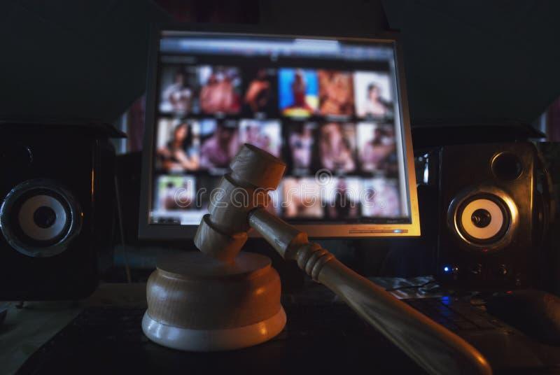 Martello sui precedenti dello schermo di computer, sito illegale con il contenuto adulto, immagini stock