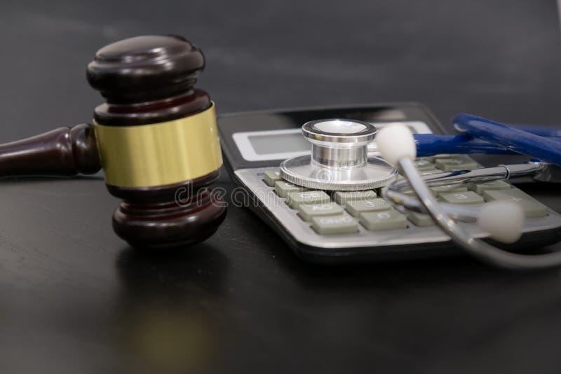 Martelo, calculadora e estetoscópio de madeira do juiz na tabela fundo preto, o conceito da negligência médica, a fotografia de stock