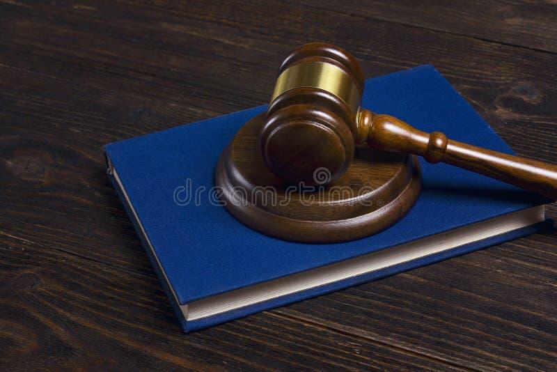 Martelo de madeira dos juizes que encontra-se no livro legal na tabela de madeira fotografia de stock royalty free
